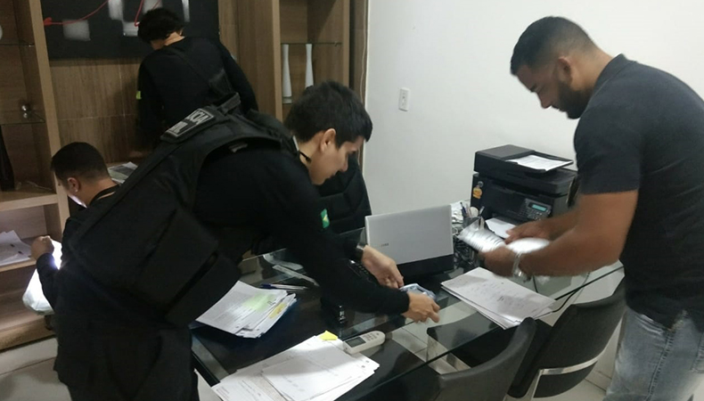 Policiais analisando documentos